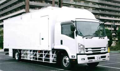カメラ機材や音声機器などを運搬するいすゞの中型車ベースの支援車もセットになっている...ザ・トラック