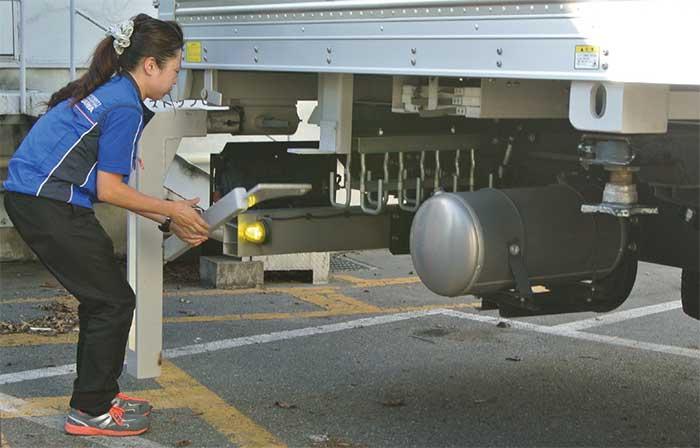 荷箱脱着作業を開始。レバーを下げ、荷箱の下に格納されていた支持脚を地面に降ろす。「支持脚は少し重いけれど、もう慣れました」...ザ・トラック